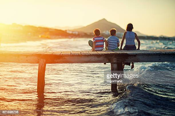 summer vacations - kids sitting on sea pier - islas baleares fotografías e imágenes de stock