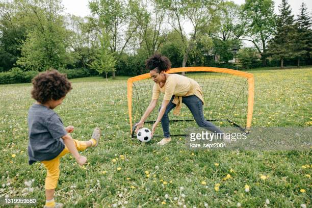 summertime activities for kids and parents - soccer game - scoring a goal stock pictures, royalty-free photos & images
