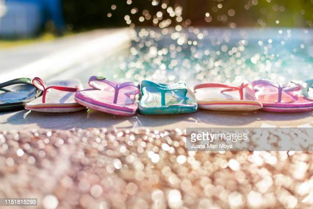 summery background, colorful group of flip flops on the edge of a pool - flip flop stock pictures, royalty-free photos & images