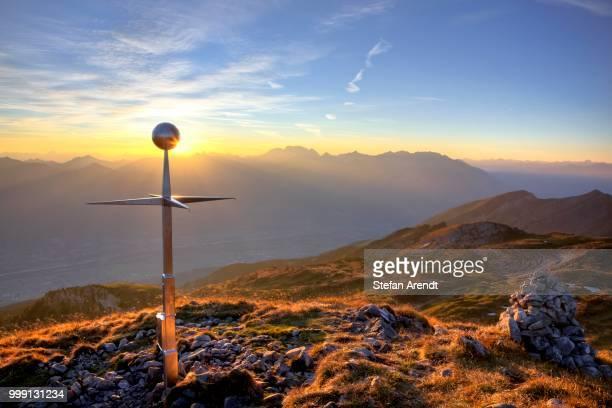 Summit cross of Mt Margelkopf above the Rhine Valley at dawn in autumn, Swiss Alps, Switzerland