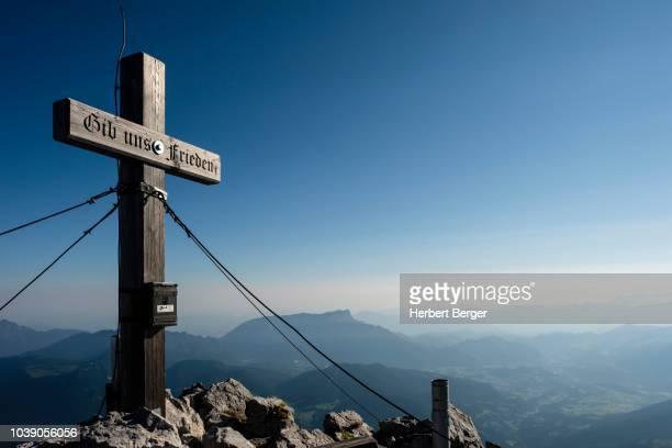summit cross of the hochkalter, 2.607m, behind the untersberg, berchtesgaden alps, ramsau, berchtesgaden national park, berchtesgadener land, bavaria, germany - berchtesgaden alps stock photos and pictures