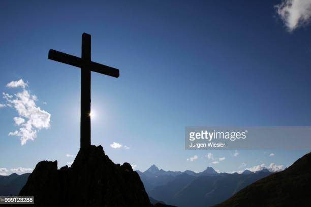 Summit cross on Nufenenpass at 2478 m, behind the Bernese Alps with Mt. Finsteraarhorn, 4274m and Mt. Lauteraarhorn, 4043m, Canton Valais, Switzerland