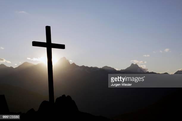 Summit cross on Nufenenpass at 2478 m, behind the Bernese Alps with Mt. Finsteraarhorn, 4274m and Mt. Lauteraarhorn, 4043m, Canton Valais, Switzerlandd