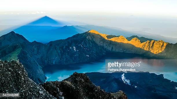 Summit of Mount Rinjani and its shadow after sunrise.