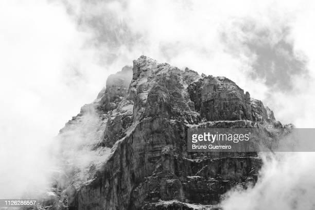 summit of snowcapped mountain in clouds - formação rochosa imagens e fotografias de stock
