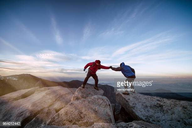 summiting mountain together as a team - california strong stock photos and pictures
