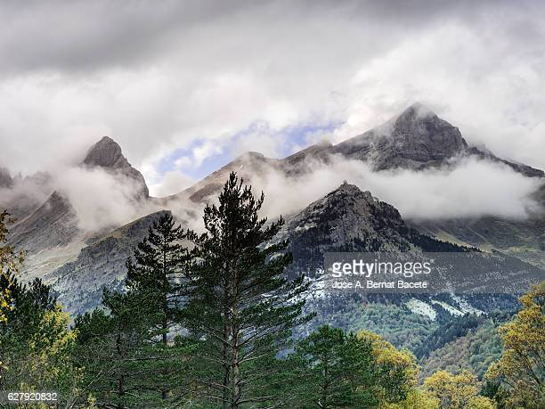 Summits of high mountains with snow in autumn and clouds of storm, in a valley of the Pyrenees