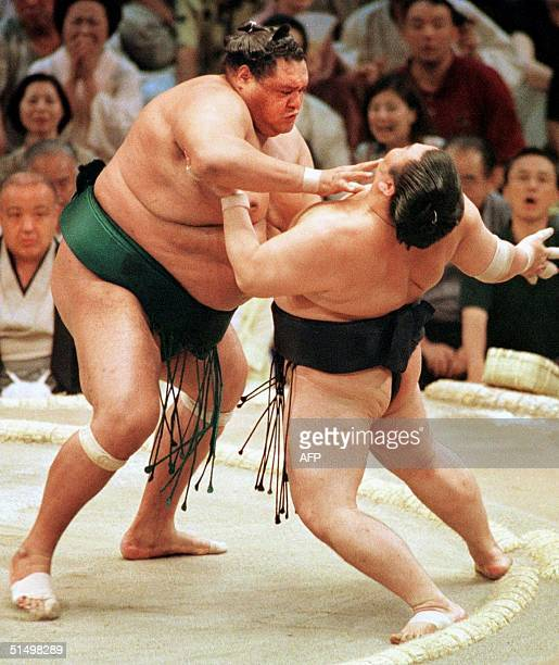 Sumo grand champion Akebono pushes Tamakasuga ranked 'komusubi' out of the ring to remain the solo unbeaten leader at 70 in the 15day Nagoya Grand...
