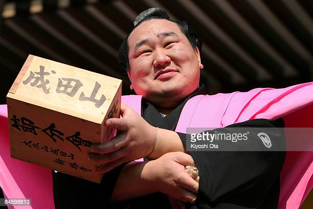 Sumo Grand Champion Asashoryu whose real name is Dolgorsuren Dagvadorj hides packs of beans under a sleeve of his hakama during a beanscattering...