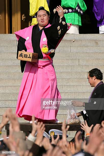 Sumo Grand Champion Asashoryu whose real name is Dolgorsuren Dagvadorj throws packs of beans to visitors during a beanscattering ceremony at...