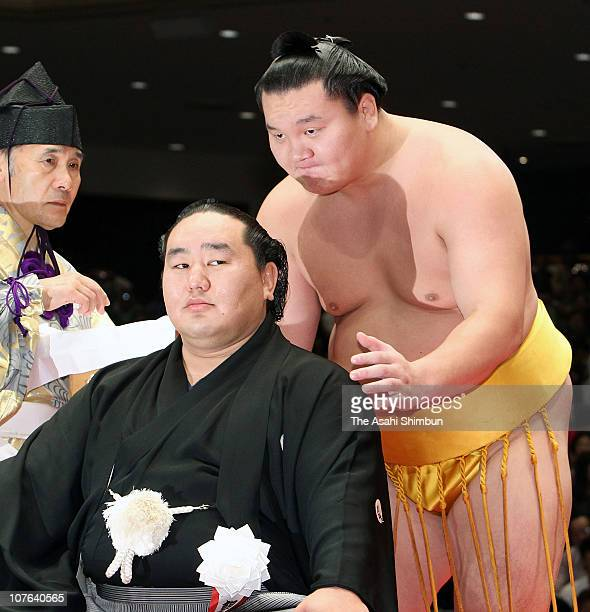 Sumo grand champion Hakuho cuts a part of the topknot of former Yokozuna sumo grand champion Asashoryu real name Dolgorsurengiin Dagvadorj during...