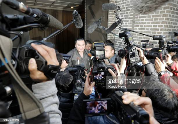 Sumo grand champion Hakuho is surrounded by the media in Fukuoka on Nov 28 after coming out of a hotel where he was questioned by police as one of...