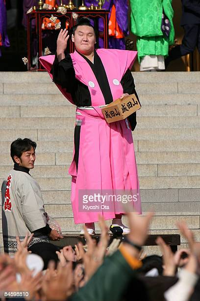 Sumo Grand Champion Hakuho whose real name is Munkhbat Davaajargal throws packs of beans to visitors during a beanscattering ceremony at Shinshoji...