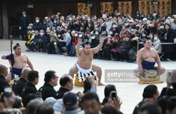 Sumo grand champion of yokozuna Kakuryu of Mongolia accompanied by tachimochi or swordbearer Nishikigi and tsuyuharai or outrider Ikioi takes part in...
