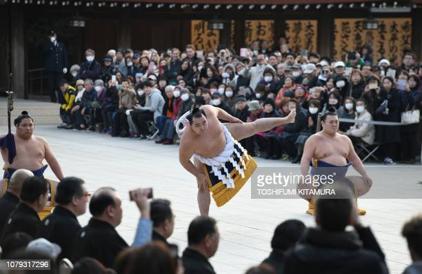 Sumo grand champion of yokozuna Kakuryu of Mongolia accompanied by tachimochi or swordbearer Nishikigi and tsuyuharai or outrider Ikioi takes part in...