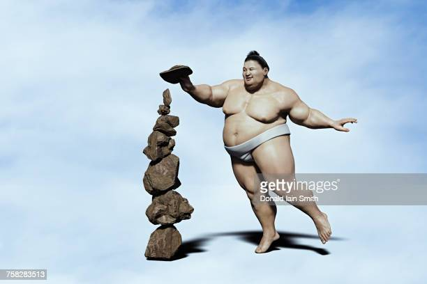 sumo wrestler balancing pile of rocks - 相撲 ストックフォトと画像