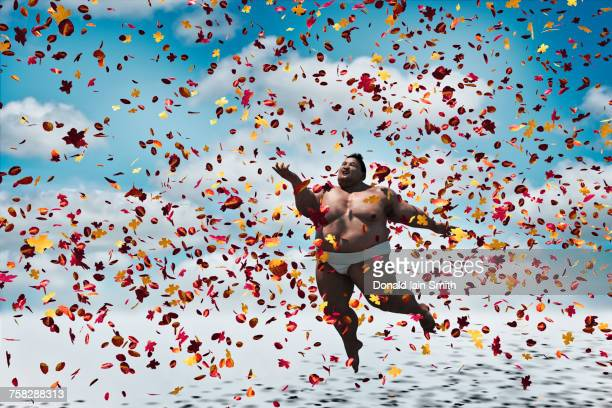 Sumo wrestler floating in autumn leaves