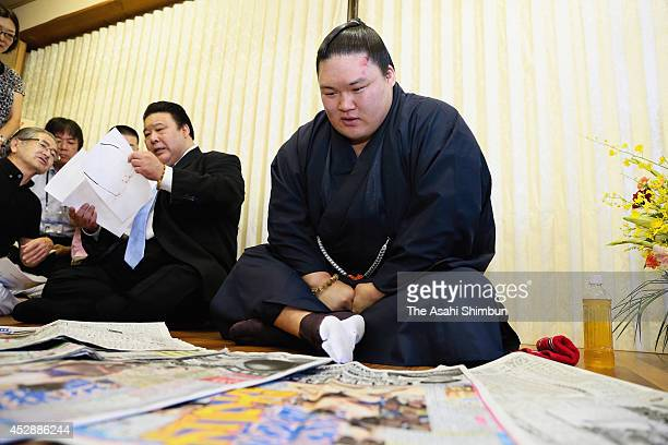 Sumo wrestler Goeido checks sport newspapers before a press conference a day after the Grand Sumo Nagoya Tournament on July 28 2014 in Fuso Aichi...