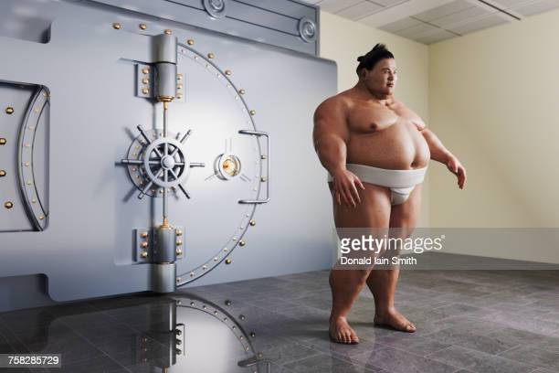 sumo wrestler guarding vault - sumo wrestling stock pictures, royalty-free photos & images