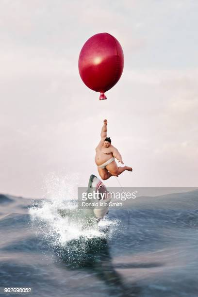 Sumo wrestler hangs from balloon above sea as great white shark leaps out of water