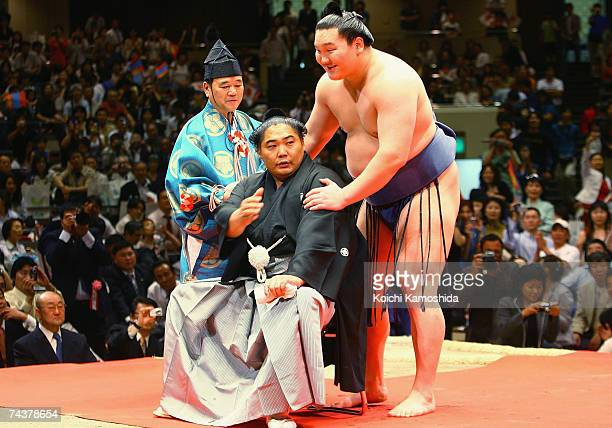 Sumo wrestler Kyokushuzan of Mongolia and ozeki Hakuho of Mongolia attend a ceremony to cut the top knot of Kyokushuzan during his retirement...