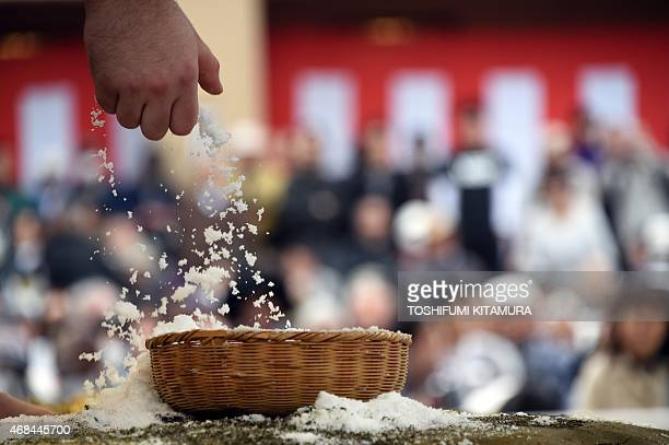 A sumo wrestler picks up a handful of salt to throw into the ring before his bout for luck during a 'honozumo' a ceremonial sumo exhibition at the...