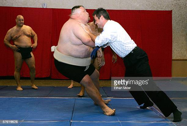 Sumo wrestler Ronny Allman of Norway watches as wrestler Casey Burns of Idaho lets Fox television sports anchor Dave Hall knock him over during a...