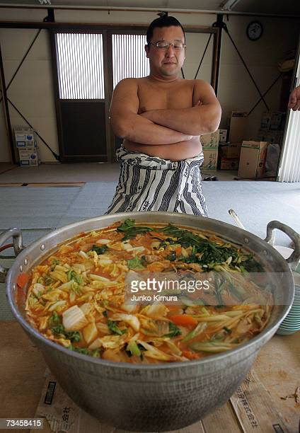 A sumo wrestler sits beside a large dish of 'chankonabe' during a 'Sumo Diet Campaign' event at Musashigawa Sumo Stable on March 1 2007 in Osaka...