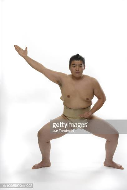Sumo wrestler standing against white background, portrait