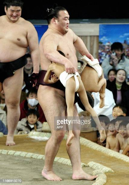 Sumo wrestler Takamisakari lifts two little sumo wrestlers to carry tem outside of the ring during an exhibition of sumo wrestling at the World Expo...