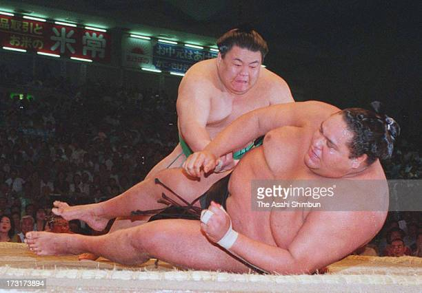 Sumo wrestler Takatoriki throws Hawaiian yokozuna, sumo grand champion Akebono, whose real name is Chad George Haaheo Rowan to win during day three...