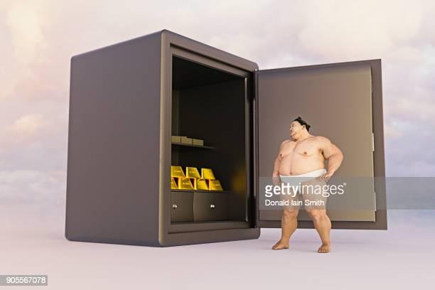 Sumo wrestler watching gold in safe