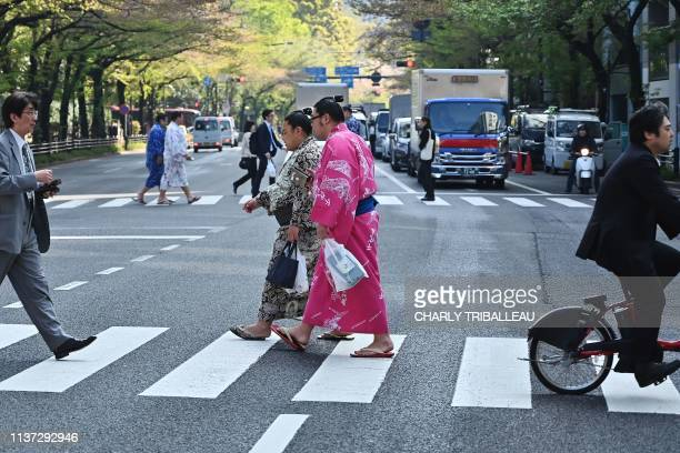 """Sumo wrestlers cross a street as they head towards the grounds of Yasukuni Shrine for a """"honozumo,"""" a ceremonial sumo exhibition, in Tokyo on April..."""