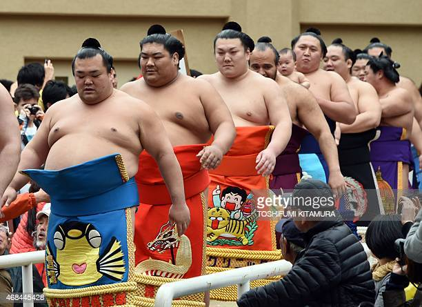 Sumo wrestlers enter the ring before their bouts during a 'honozumo' a ceremonial sumo exhibition at the Yasukuni shrine in Tokyo on April 3 2015...