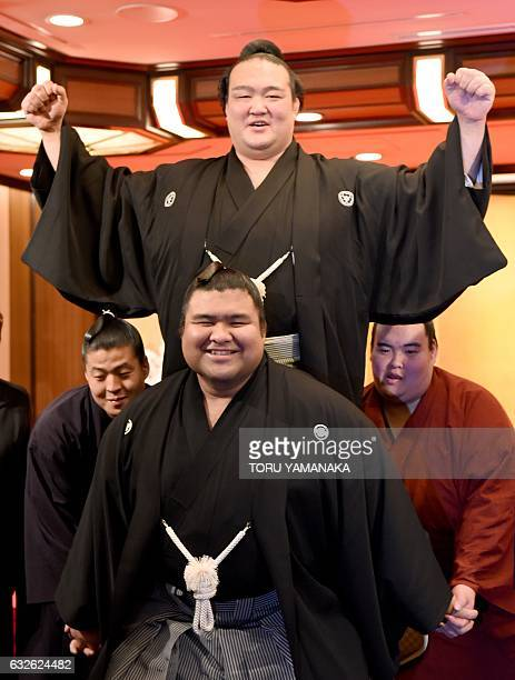 Sumo wrestlers from his stable hold up Kisenosato to celebrate his promotion to sumo's highest rank of 'yokozuna' or grand champion in Tokyo on...