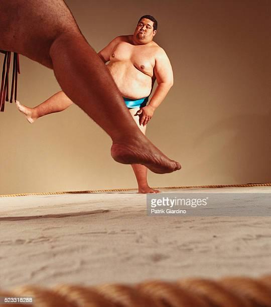 sumo wrestlers lifting legs before fight - sport da combattimento foto e immagini stock