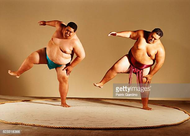 Sumo Wrestlers Lifting Legs