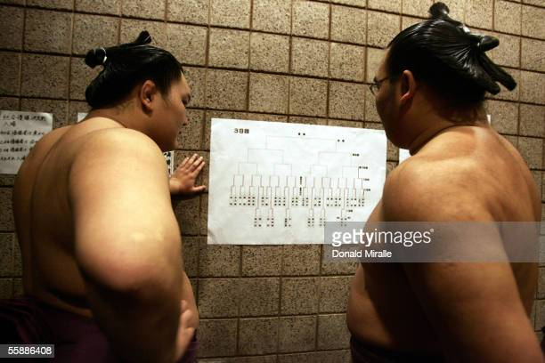 Sumo wrestlers look at seedings and results during the Grand Sumo Championship on October 9 2005 at Mandalay Bay Events Center in Las Vegas Nevada