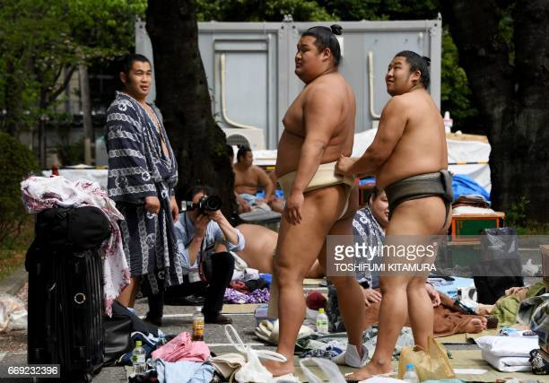 Sumo wrestlers prepare ahead of a 'honozumo' a ceremonial sumo exhibition on the grounds of Yasukuni Shrine in Tokyo on April 17 2017 Sumo's top...