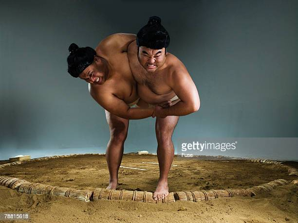 sumo wrestlers struggling for victory - sumo wrestling stock pictures, royalty-free photos & images