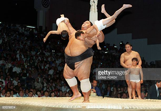 Sumo wrestling champion Konishiki from Hawaii lifts two children from a sumo wrestling school in San Jose 05 June before the start of the first day...