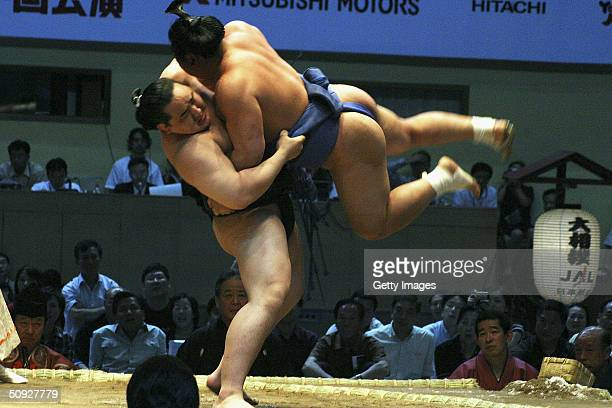Sumo wrestling superstar Asasyoryu lifts his oppponent during a sumo tournament on June 5 2004 in Beijing China A total of 111 sumo wrestlers are in...