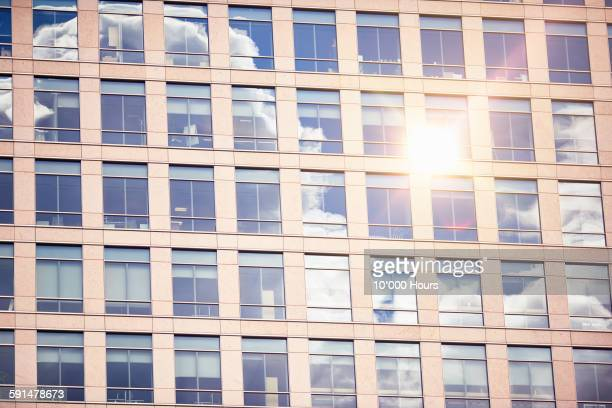 Sun and cloud reflected in office building