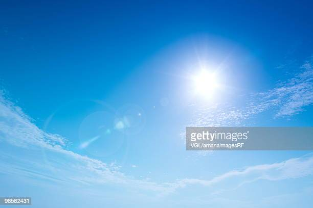 Sun and clouds in blue sky, lens flare, copy space