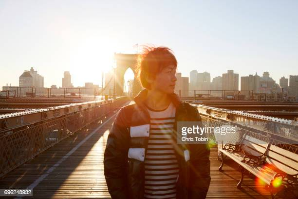 Sun and lens flare in background of young man standing on Brooklyn Bridge