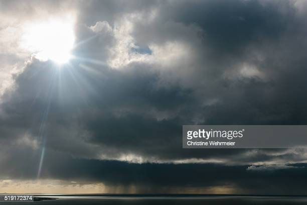 sun and rain and storms over the ocean - christine wehrmeier stock pictures, royalty-free photos & images