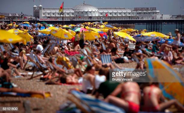Sun bathers are seen on a packed Brighton Beach June 19 2005 in Brighton England Temperatures are likely to soar to 33C in London with similar highs...