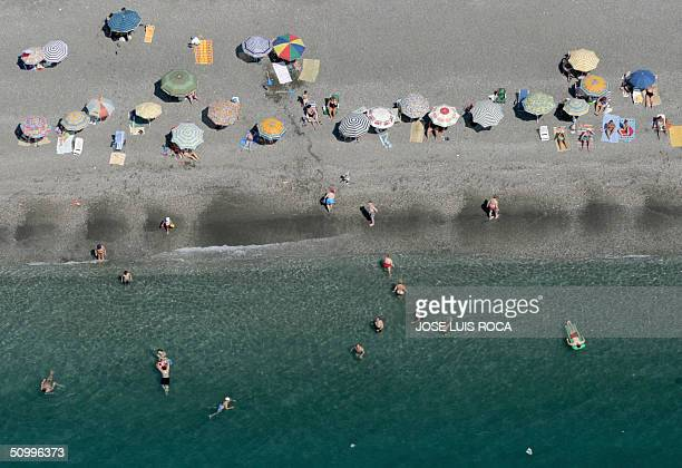 Sun bathers enjoy sunny day at Torre del Mar beach in Malaga southern Spain 25 June 2004 AFP PHOTO/ JOSE LUIS ROCA