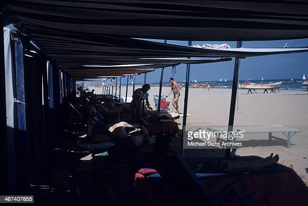 Sun bathers lay under canapies by the Lido in Venice Italy