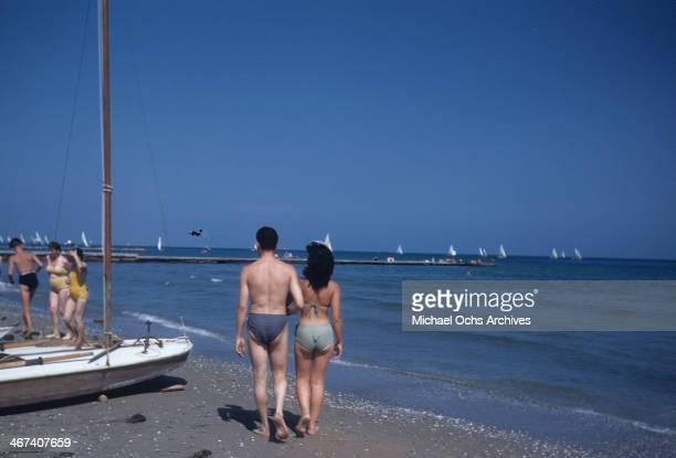 Sun bathers walk the Lido in Venice Italy